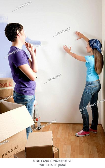 Young couple discussing where to place objects on wall