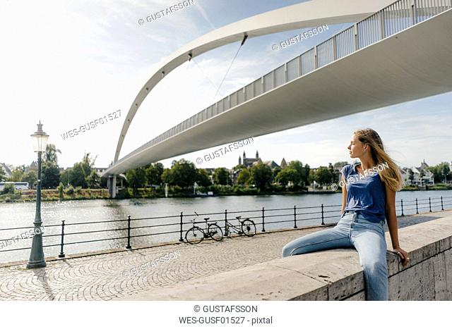 Netherlands, Maastricht, young woman sitting on a wall at the riverside