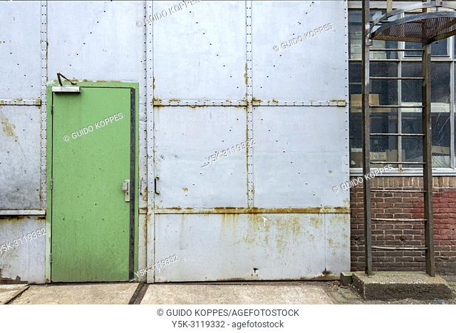 Rotterdam, Netherlands. A blue door inside an industrial, 1950's build industrial warehouse, suited for recieving trucks and large cargo's for storage and...