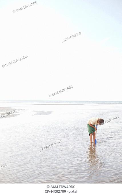 Boy with shovel playing in ocean surf on summer beach