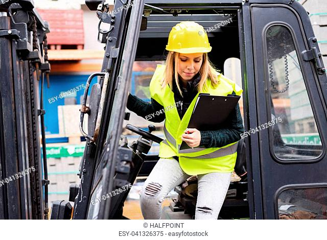 Female forklift truck driver outside a warehouse. A woman getting out of the fork lift truck, holding notes