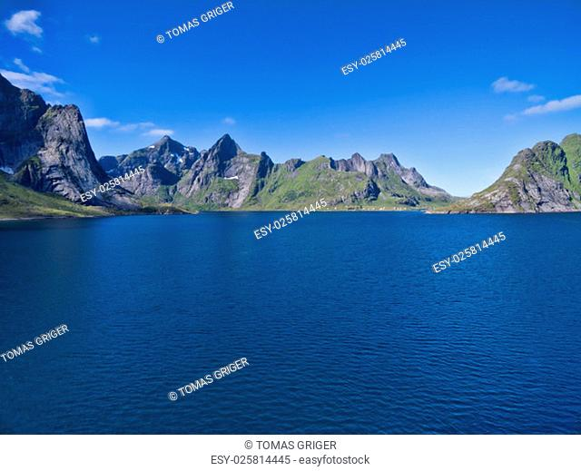 Norwegian fjord surrounded by mountain peaks on Lofoten islands