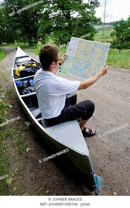 Man sitting on canoe and looking at map