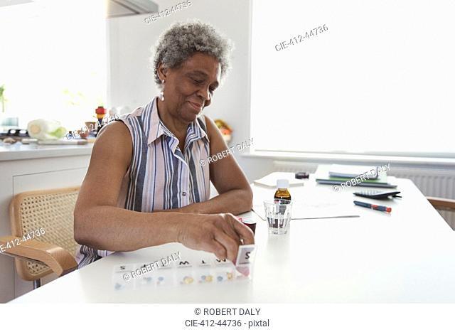 Senior woman organizing pill box at kitchen table