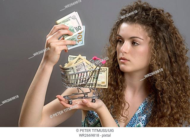 Concept of the cost of living a woman with serious expression holding supermarket trolley full of cash