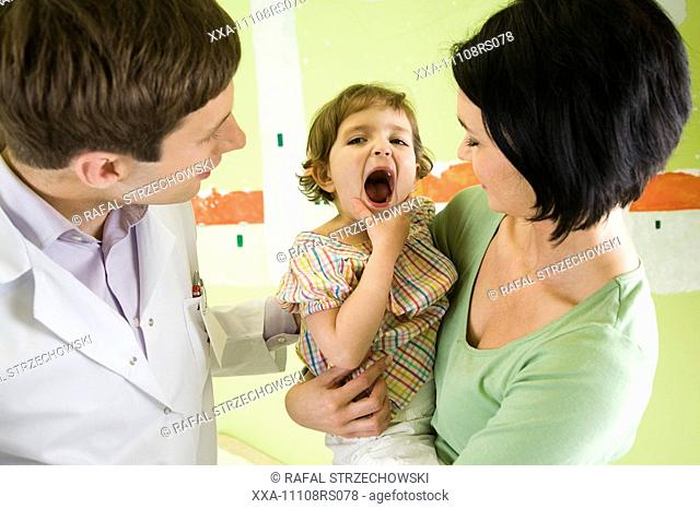 mother and daughter talking to doctor in exam room