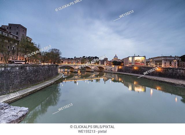 Dusk lights on Lungo Tevere with bridge Umberto I and Basilica di San Pietro in the background Rome Lazio Italy Europe