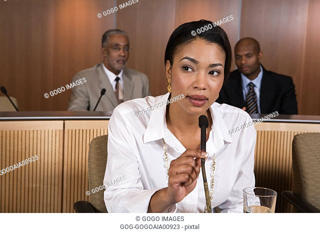 African businesswoman speaking into microphone
