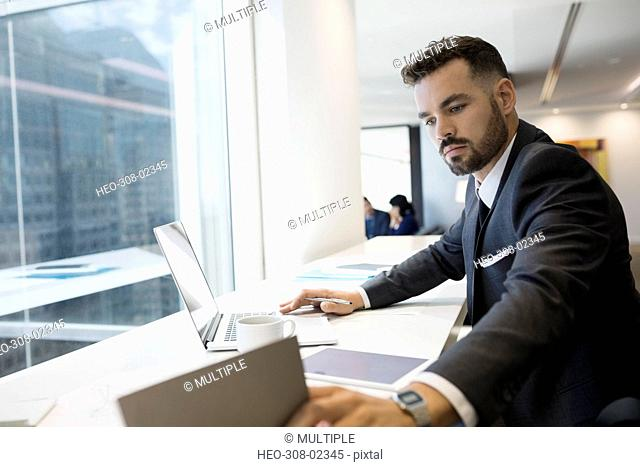 Businessman working at laptop at urban office window