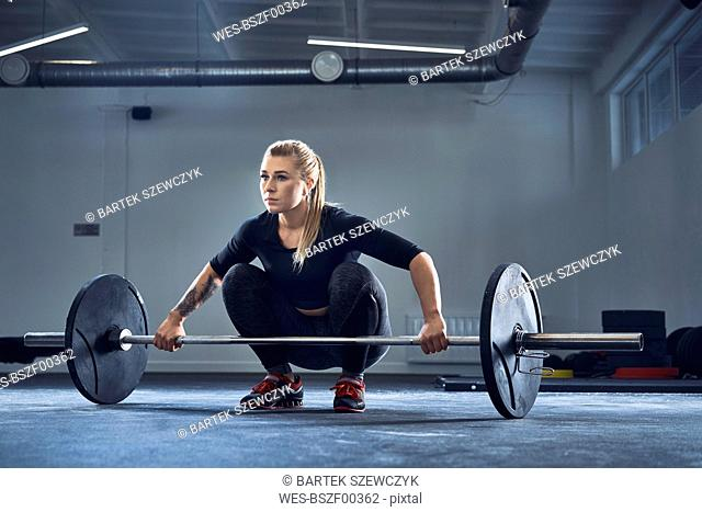 Woman doing barbell exercise at gym during weight lifting workout