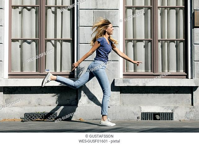 Netherlands, Maastricht, happy blond young woman running along building in the city