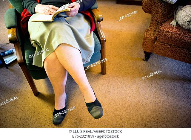 Closeup of an elderly lady legs resting sitting in an armchair and reading a book on a cottage in Yorkshire, England, UK