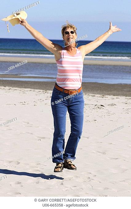 Senior woman 55 jumping for joy at the beach