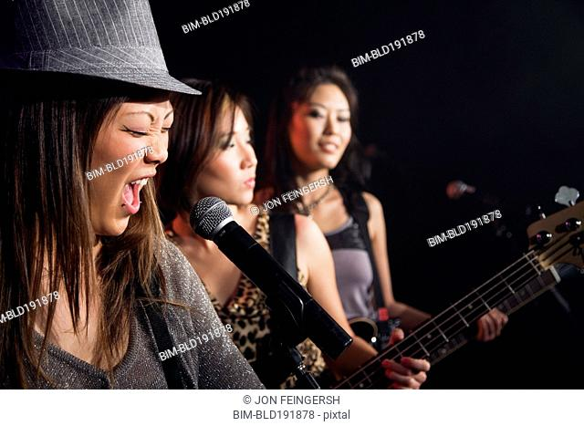 Asian women singing and playing guitar onstage