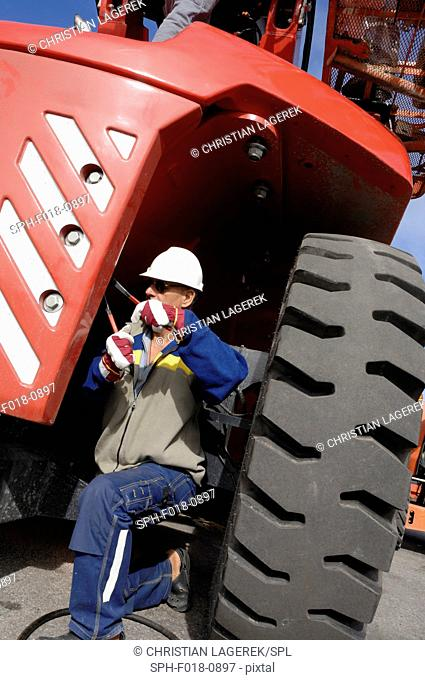 MODEL RELEASED. Mechanic by industrial vehicle with large tyre