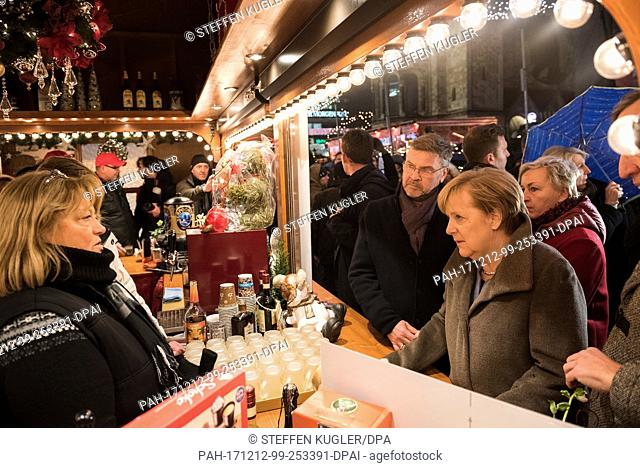 HANDOUT - German chancellor Angela Merkel (R) of the Christian Democratic Union party (CDU) visits the Breitscheidplatz almost one year after the terrorist...
