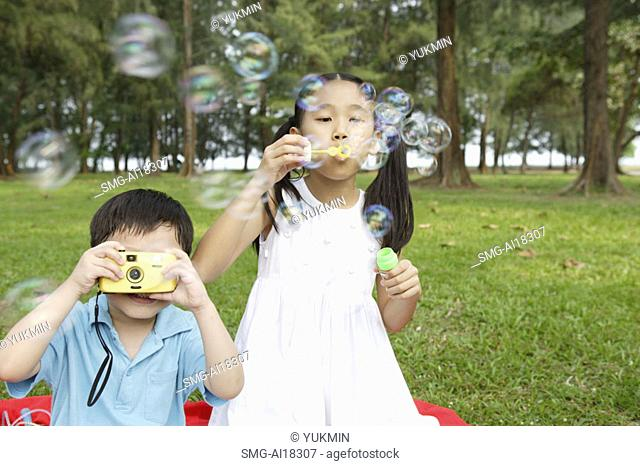 Girl blowing bubbles, boy taking pictures with camera