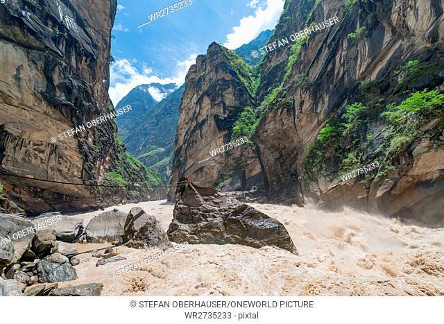 China, Yunnan Sheng, Diqing Zangzuzizhizhou, hike (2-day tour) to the Tigersprung Gorge of the Yangtze River, bridge to a boulder in the wild Yangtze River