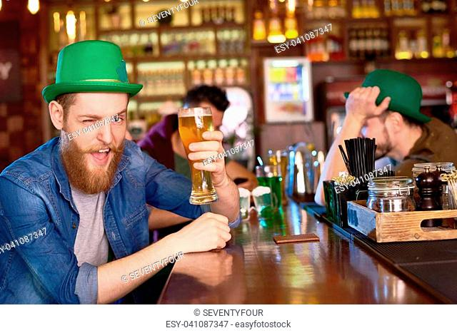 Cheerful bearded man wearing green bowler hat holding beer glass in hand and winking at camera while celebrating St. Patricks Day in pub, portrait shot