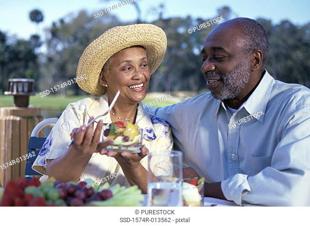 Senior woman holding a bowl of fruit salad with a senior man sitting beside her