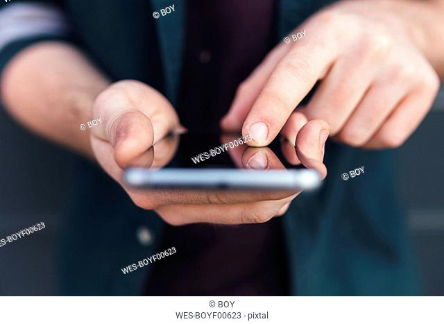 Index finger of young man touching smartphone