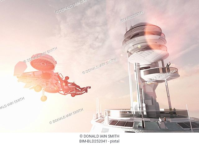Man in futuristic tower waving to flying vehicle