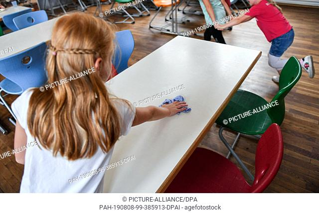 07 August 2019, Berlin: A pupil wipes the table after lunch in the cafeteria of the primary school at Wuhlheide. Photo: Jens Kalaene/dpa-Zentralbild/ZB
