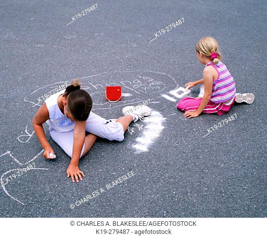 Young girls drawing on pavement with chalk. Anacortes, Skagit County. Washington, USA