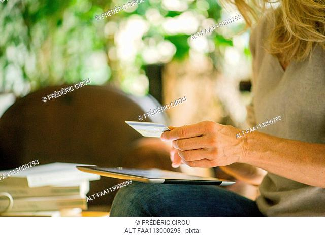Woman using digital tablet and credit card, cropped