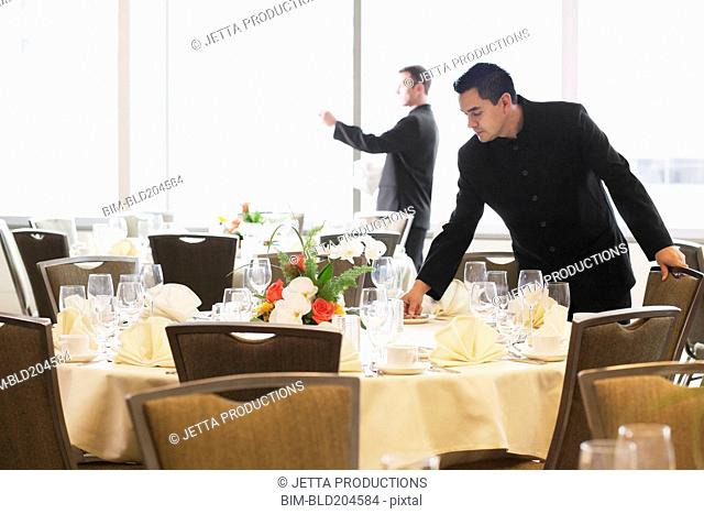 Waiters setting tables in dining room