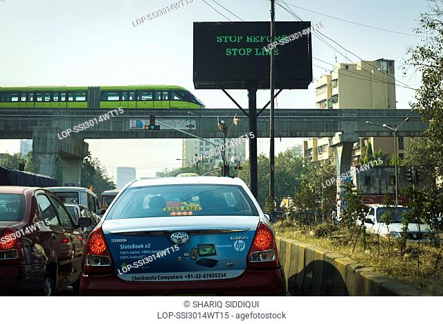 India, Maharashtra, Mumbai. A monorail undergoing safety trials over a busy road junction