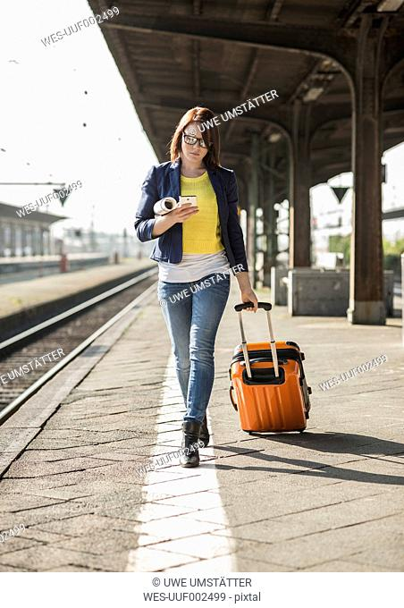 Young woman with cell phone and baggage at train station