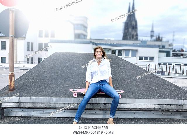 Germany, Cologne, portrait of smiling young woman sitting on roof terrace