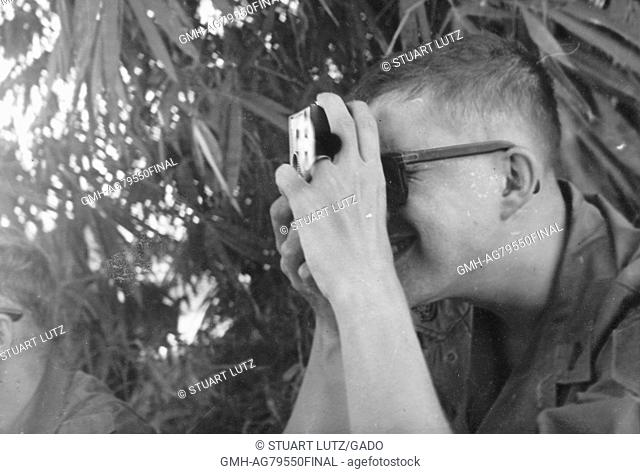 A United States Army soldier smiling while he is using a personal camera to take a photograph, another soldier and tropical foliage are visible nearby, Vietnam