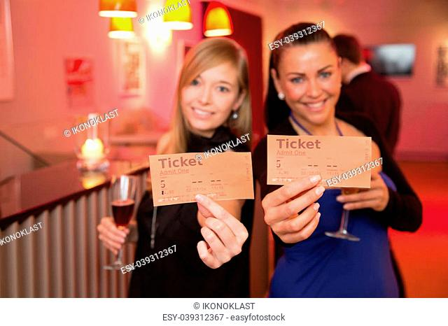 Two beautiful women presenting tickets for a theatre, cinema or a concert