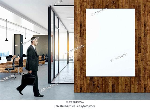Side view of young businessman walking in modern office interior with empty poster on wall. Mock up, 3D Rendering