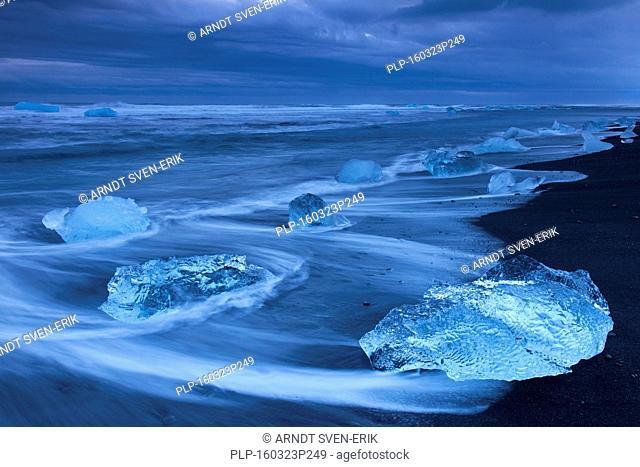 Melting blocks of ice washed on beach along the Atlantic Ocean coastline at Breidamerkursandur black sands in winter, Sudursveit, Iceland