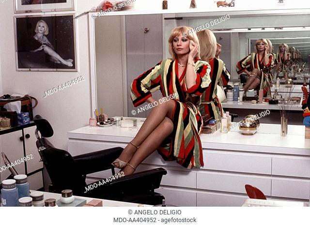 Raffaella Carrà in her dressing room. Italian TV presenter, actress, singer and showgirl Raffaella Carrà (Raffaella Maria Roberta Pelloni) sitting on a chest of...