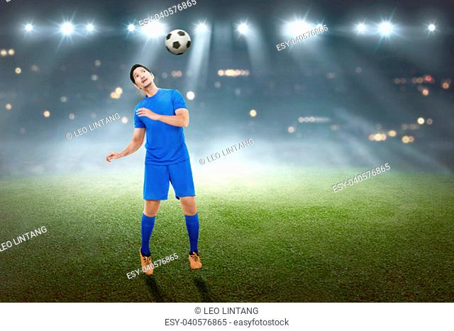 Handsome asian male football player trying to heading the ball in the match