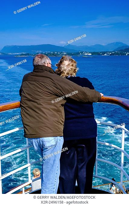 A couple looking back over a ships rail whilst leaving port in the Norwegian fjords
