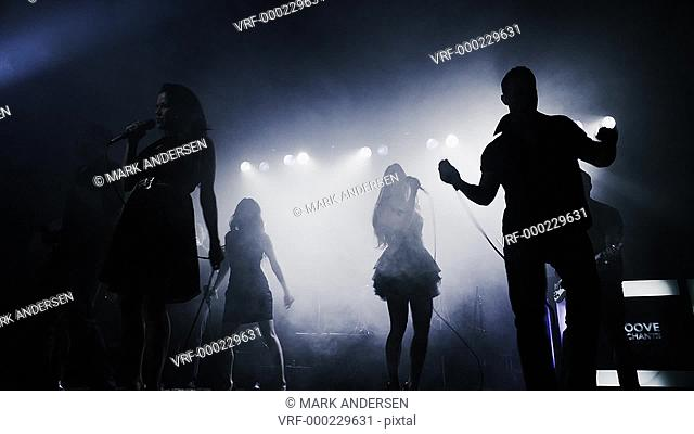 Panning shot of silhouetted singers and musicians performing on stage / Spanish Fork, Utah, United States