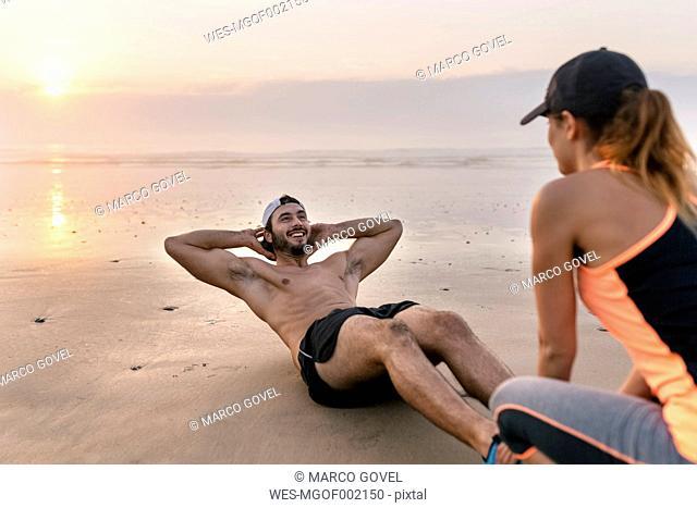 Athletes couple training on the beach at sunset