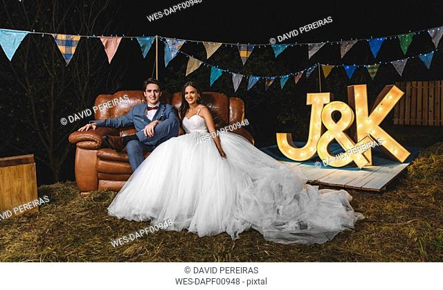 Portrait of happy wedding couple sitting on sofa on a night field party