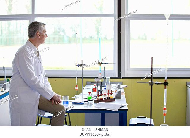 Pensive chemistry teacher looking out science classroom window