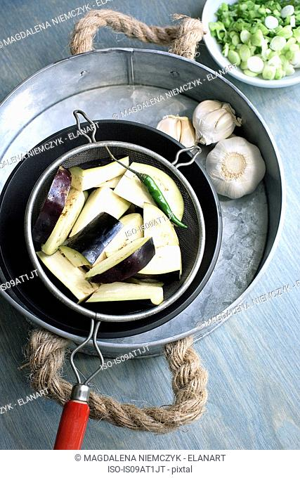 Still life of sieve with sliced aubergines, green chillies and garlic bulb