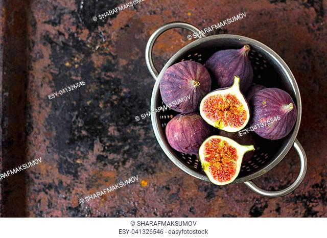 Top view of figs fruits inside metal colander on table