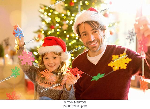 Portrait smiling father and daughter in Santa hats holding string of paper snowflakes