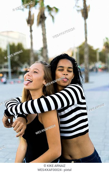 Two playful young women on square
