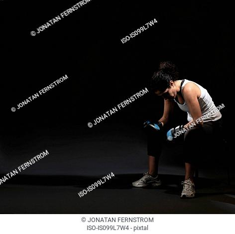 Female boxer sitting against black background
