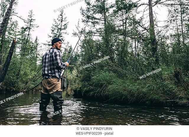 Angler standing in river with waders